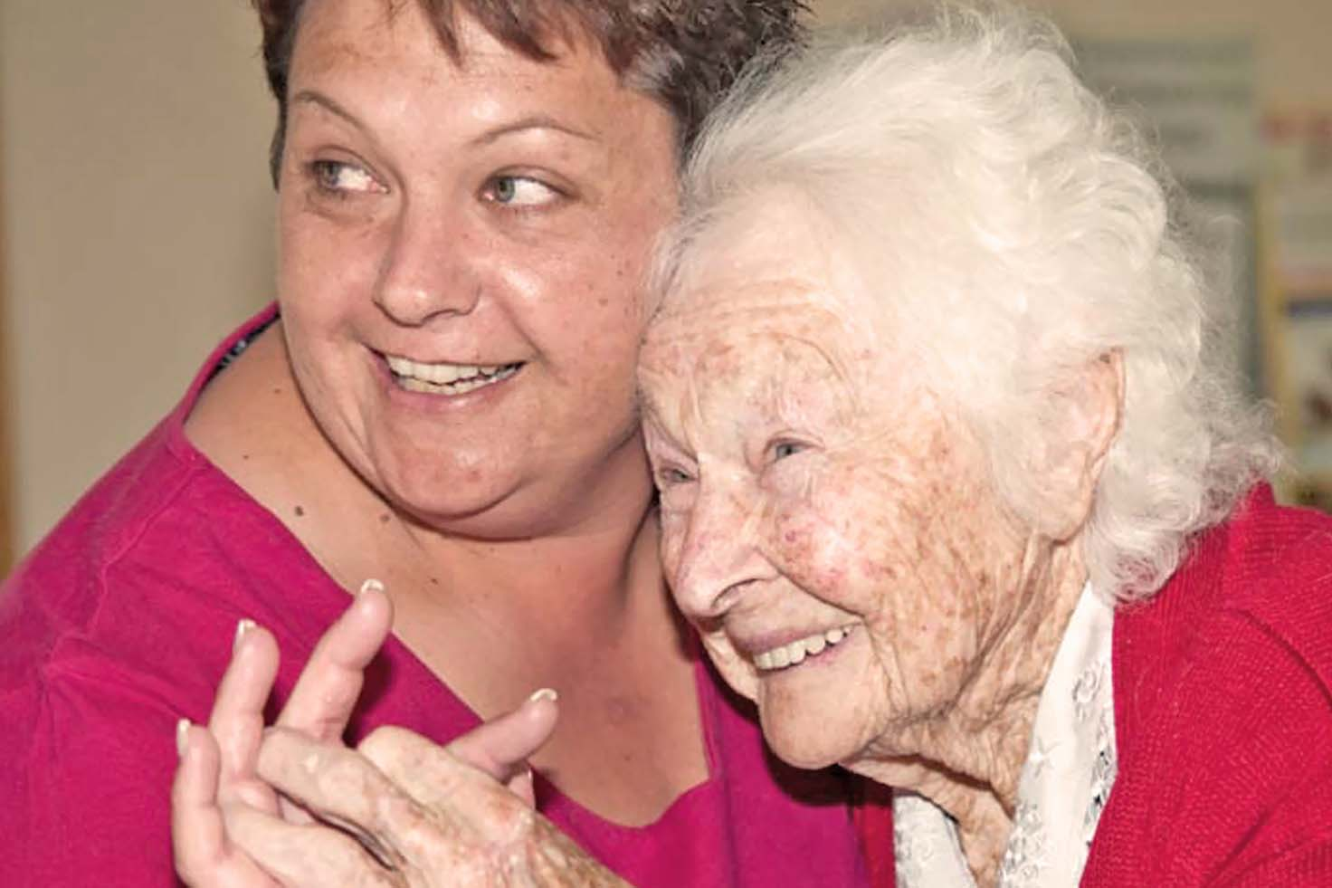 Elderly lady and a younger woman hugging