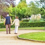 Older couple walking through the park holding hands